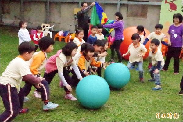 小朋友用力翻滾大球,開心迎接兒童節。(記者林國賢攝)