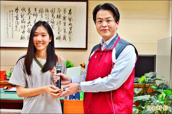 「暨中小張鈞甯」李榆文(左)獲得全國聲樂比賽第一名,校長張正彥(右)送給她一支麥克風。(記者陳鳳麗攝)