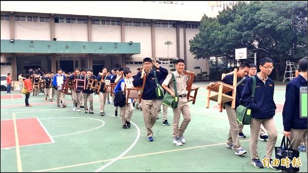新竹高中兩百多名學生扛著自己的座椅,體驗九十年前學長從學校原址新竹女中搬遷到新竹高中現址的歷程。(記者洪美秀攝)