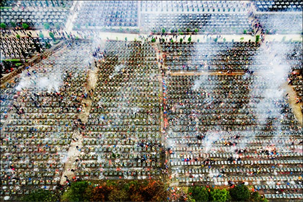 中國江西省撫州市一處公墓,四日在清明節掃墓這天燃燒大量紙錢。(路透)