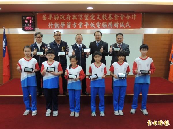 台灣信望愛文教基金會捐贈苗栗縣國中小15校、976台HTC Flyer平板電腦及Learn Mode數位學習平台,由縣長徐耀昌(後排中)及新港國中小學生代表接受。(記者張勳騰攝)
