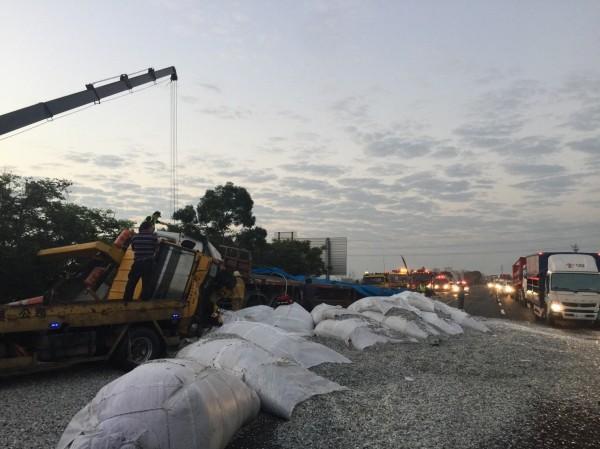 拖板車追撞消防車後翻覆,車體嚴重受損,載運的塑膠粒傾瀉在國道上。(記者湯世名翻攝)