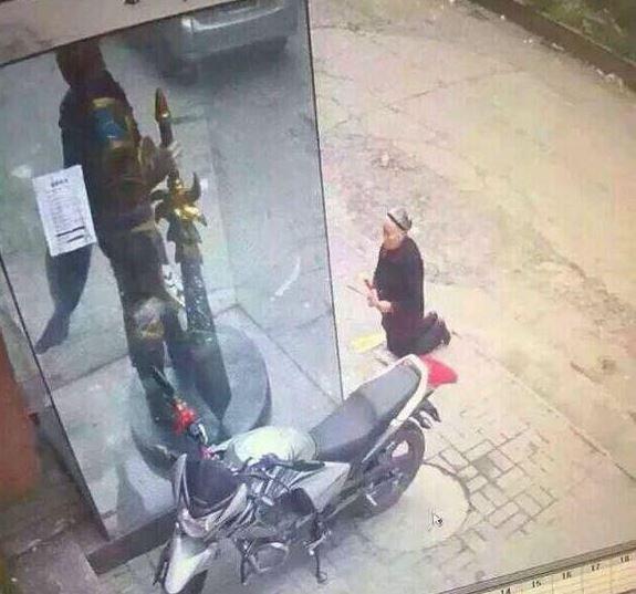 中國老婦當街跪拜網咖前的英雄聯盟人物雕像。(圖擷取自3DMGame)