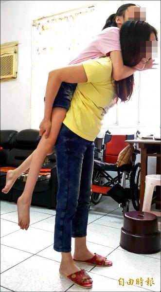 女童脊椎側彎S型又無法走路,單親母每天忍痛揹四樓。(記者陳文嬋攝)