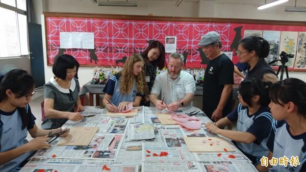藝術家陳三火(戴帽者)教導民德國中及澳洲姐妹校梅洛斯中學師生剪黏。(記者劉婉君攝)