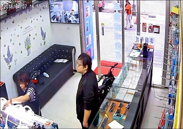 吳女(左)兜售偷來的手機,一旁是蕭姓店員。 (記者余衡翻攝)