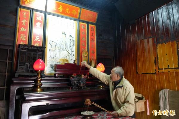 雖然百年神像已被偷,負責看顧的長者照樣上香。(記者劉曉欣攝)