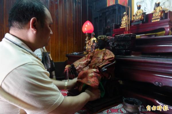 妝佛師傅幫百年軟身神像陳靖姑進行安座整理。(記者劉曉欣攝)