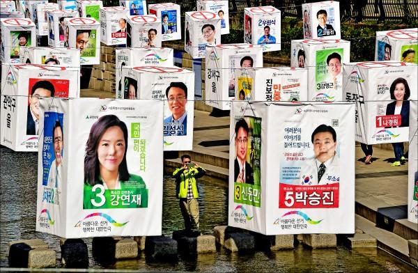 南韓十三日將舉行國會選舉,首爾著名景點清溪川滿是候選人的文宣品。根據蓋洛普民調,總統朴槿惠所屬的新世界黨支持度目前為三成九,主要反對黨為二成一,還有兩成還沒決定支持對象。這次大選,被稱為「三無世代(無工作、無房子及無結婚前景)」的年輕選民可能扮演影響朝野兩大黨政治勢力消長的重要角色。分析家預測新國會三百席中,新世界黨席次可望在一五○至一八○席之間。(法新社)