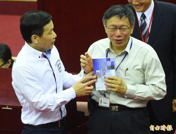 台北市長柯文哲12日赴市議會進行施政報告,一開始就遭到杯葛,國民黨議員鍾小平送上一本三民主義,要柯市長讀一讀。(記者張嘉明攝)