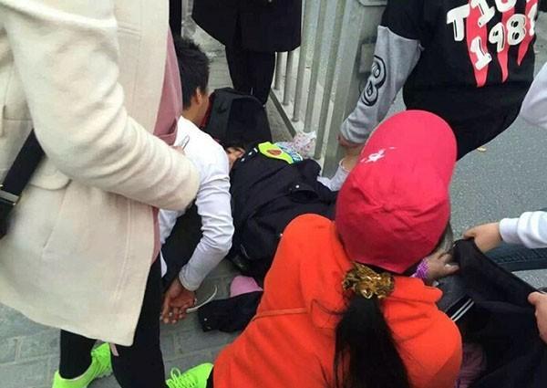 一名孕婦在街頭倒地痛苦不已,當地民警及熱心群眾利用人牆遮擋、防彈背心當床墊,攜手搭起臨時產房,讓女子順利生產。(圖擷取自澎湃新聞)