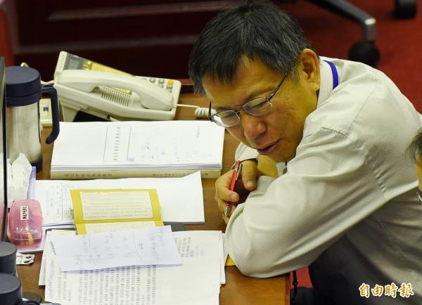 台北市長柯文哲今天(12日)赴市議會進行施政報告,卻被議員發現在讀佛經,引發不滿。(記者張嘉明攝)