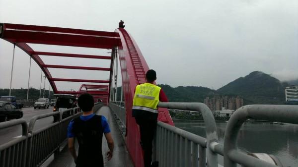 簡男爬上關渡橋巨拱企圖輕生,與救援警消對峙。(記者黃捷翻攝)