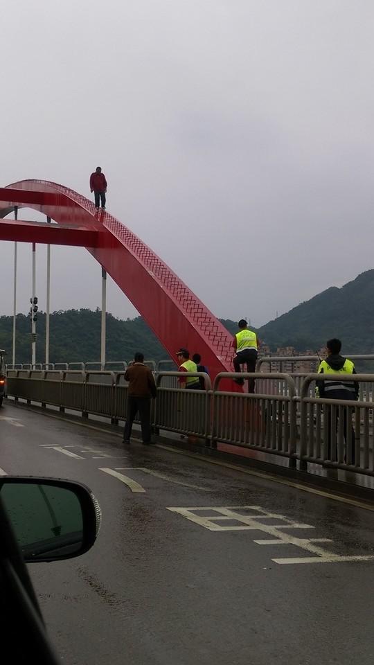 簡男爬上關渡橋巨拱企圖輕生,與救援警消對峙。(記者黃捷翻攝自臉書「細說淡水」。)