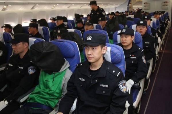被中國在肯亞強押的45名台灣人,今天被戴上黑色頭套,飛抵北京。(圖擷自中國官媒《新華社》)