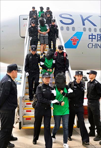 中國新華社十三日刊登在肯亞涉入電信詐騙案的第二批嫌疑人,被押解回中國的照片,每名頭戴黑色頭套、雙手被銬的嫌疑人,各被兩名警察控制。(美聯社)