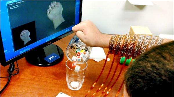 藉由腦波訊號繞過受傷脊髓的方式,讓癱瘓的患者恢復動作。圖為四肢癱瘓的伯克哈特展示倒出骰子。(法新社)