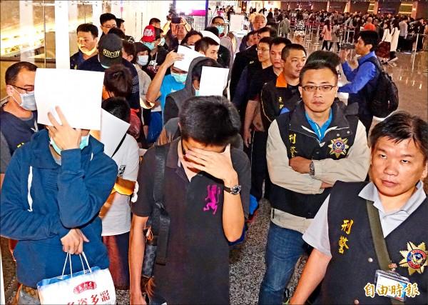 廿名遭大馬遣返的我國籍詐欺嫌犯於昨夜搭機返抵桃園機場,刑事局派員分批訊問。(記者朱沛雄攝)