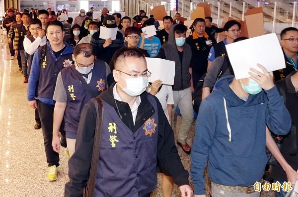 20名遭馬來西亞警方逮捕的電信詐欺犯嫌15日晚間抵桃園機場,刑事局動員20餘名警力,將相關人等分批訊問。(記者朱沛雄攝)