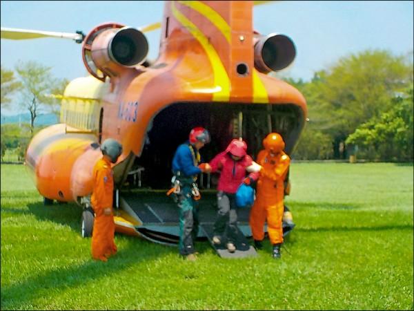 女登山客由搜救人員攙扶下直升機。(記者李忠憲翻攝)