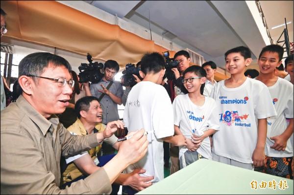 台北市長柯文哲出席北投國小女籃參加教育盃比賽18連霸頒獎活動,並為球員簽名。(記者方賓照攝)
