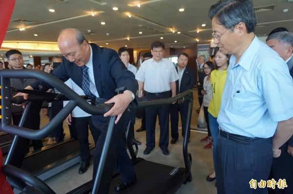 喬山公司董事長羅崑泉示範田徑選手使用的重量訓練機。(記者歐素美攝)