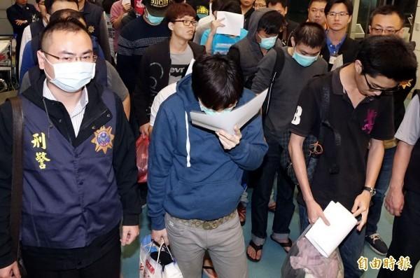 圖為20名涉案國人15日抵達機場後,接受警方盤查。(資料照,記者朱沛雄攝)