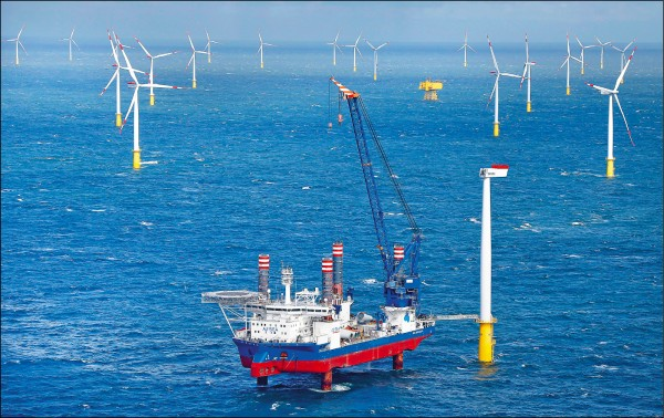 ▲發展國產自製風力發電機,是我國綠能政策重要方向。「新能」公司擬專案進口中國測試風機,因無法談妥技術移轉,已於上週遭到經濟部工業局否決。圖為去年九月間一艘平台工作船在德國北海離岸風電場安裝風力發電機。(路透檔案照)