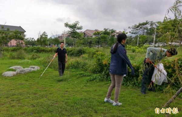 台東大學教官持捕蛇鋏在草地尋覓蛇蹤。(記者黃明堂攝)
