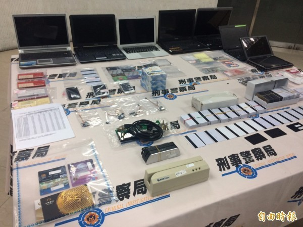 警方起獲磁卡讀寫器、磁卡、空白卡、犯案手機、筆電等大批贓證物。(記者邱俊福攝)