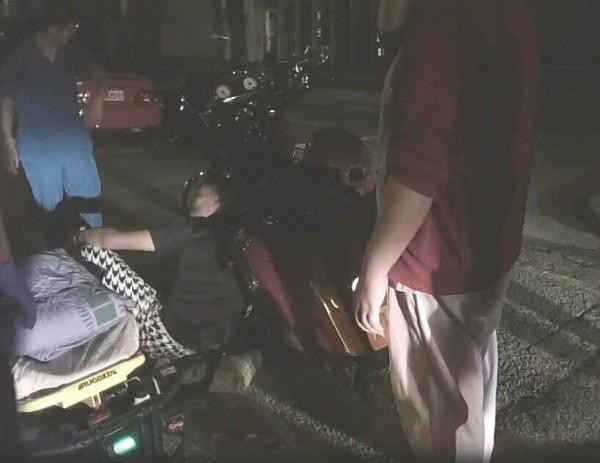 「亂入哥」(蹲者)酒駕自撞倒在路邊,腿部疑似被排氣管燙傷。(記者何宗翰翻攝)
