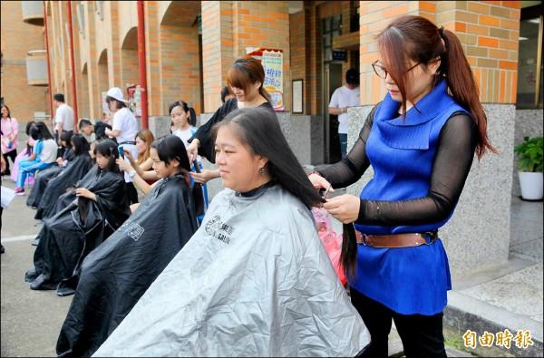 草屯國小慶祝母親節,發起學生捐長髮助癌童,髮型設計師來義剪,家長許嘉真(坐者右一)也來響應,現場剪下長髮。(記者陳鳳麗攝)