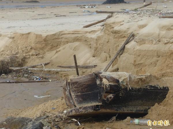 金門東割灣岸際一副棺木從沙堆中露出,讓經過的民眾有些「驚驚」(記者吳正庭攝)