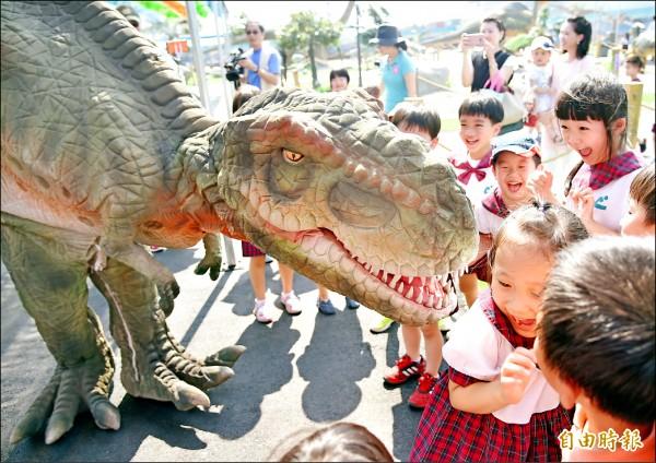 亞洲最大的「高雄侏儸紀樂園」恐龍展,明天在夢時代對面廣場登場,小朋友喜歡恐龍但是又愛又怕,親近牠又怕被牠「咬」。(記者張忠義攝)