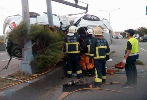 休旅車卡在路燈上,消防員搶救車內2名傷患。(記者湯世名翻攝)