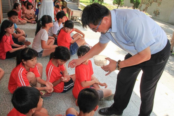 豐榮國小校長李秉承把甲魚蛋分送給每位學童。(豐榮國小提供)