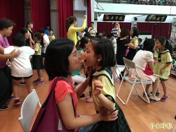 西螺文昌國小學童與媽媽一起吃巧克力捲,親子親密互動好溫馨。(記者黃淑莉攝)
