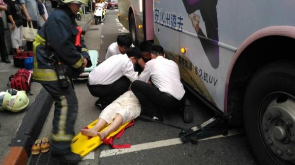 陳姓婦人遭公車撞上後,卡在2前輪間,警消到場後將其救出。(民眾提供)