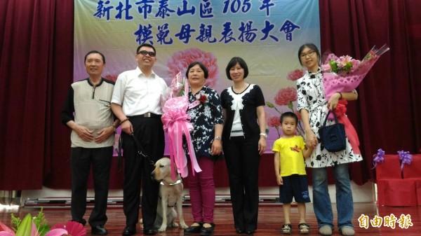 泰山區公所今表揚模範母親,視障音樂家許清閔(左二)的媽媽吳玩姿(左三)獲獎,一家人上台合影。(泰山區公所提供)