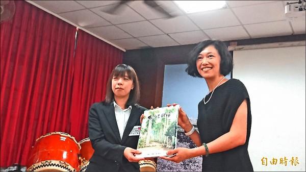 嘉南國小校長張維文(右)與日本花園小學老師互贈學生作品及學校出版的繪本。(記者劉婉君攝)