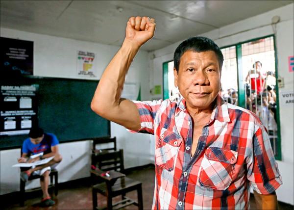 杜特蒂九日在達沃市投完票後,舉手握拳為自己打氣,投票所外擠滿想捕捉他一舉一動的媒體。(美聯社)