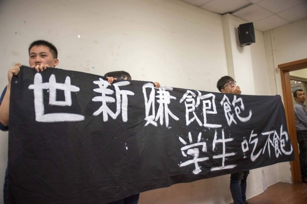 世新大學針對調漲學費舉辦公聽會,10名勞動權益行動小組學生舉布條至現場抗議。(世新大學新聞人報社提供)