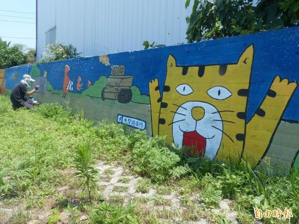 呂士昂應邀在水果餐廳圍牆繪製卡努遊金門。(記者吳正庭攝)