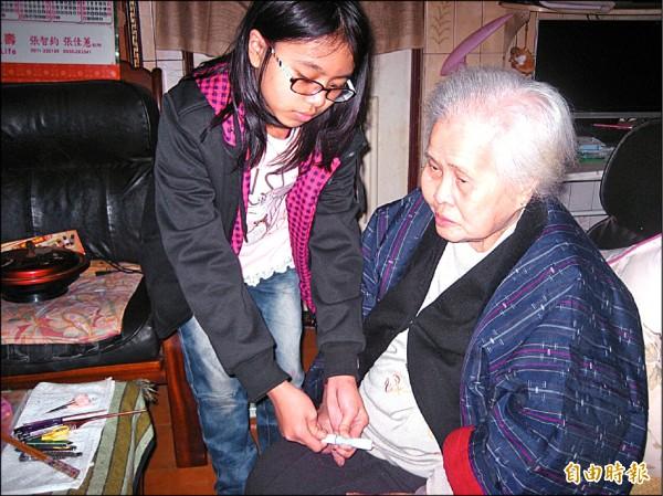 港西國小小六女學生楊敏佳學習操作腹膜透析機器,照顧洗腎九十四歲阿嬤,經常一夜不能成眠。(記者俞肇福攝)