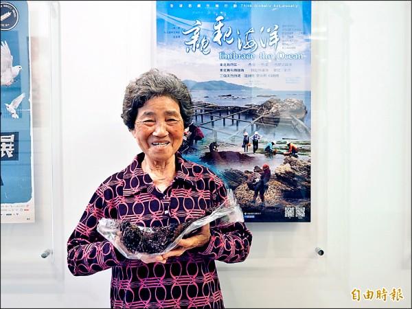 七十八歲國寶級海女吳月雲手持採集的石花菜,開心分享當海女的生涯。(記者賴筱桐攝)