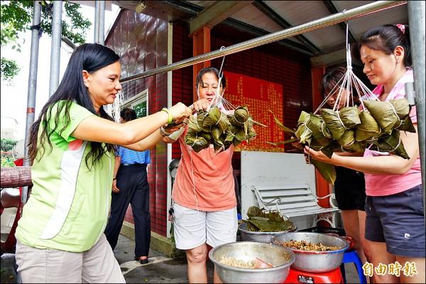 彰化縣議員賴清美(左)昨天小露身手,參與愛心包粽送家扶兒活動。(記者劉曉欣攝)
