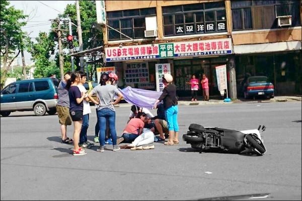謝女車禍倒地,5名高中生從廚具店跑出幫忙,2名騎車路過的婦人趕緊上前協助,並撐開雨衣為謝女遮陽。(記者湯世名翻攝)