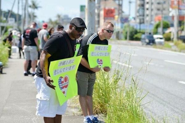 美軍姦殺沖繩女性一案震驚日本,居住在沖繩的美國一般民眾最近則站在道路旁列隊,每個人都掛上道歉的標語,對來來往往的車流鞠躬表示歉意。(圖擷自PTT)