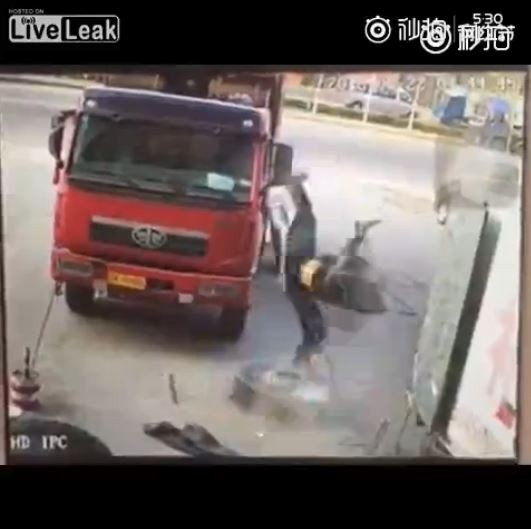 中國某修車廠的技工在檢查輪胎時,輪胎突然爆裂,技工則被輪胎內的空氣沖到半空中翻滾落地。(圖擷取自影片)