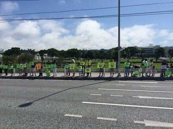 從照片上可以看到約有將近20名美國人在公路旁,以鮮綠或純白底色的紙張寫出「與沖繩同悲」、「為沖繩祈禱」。(圖擷自PTT)